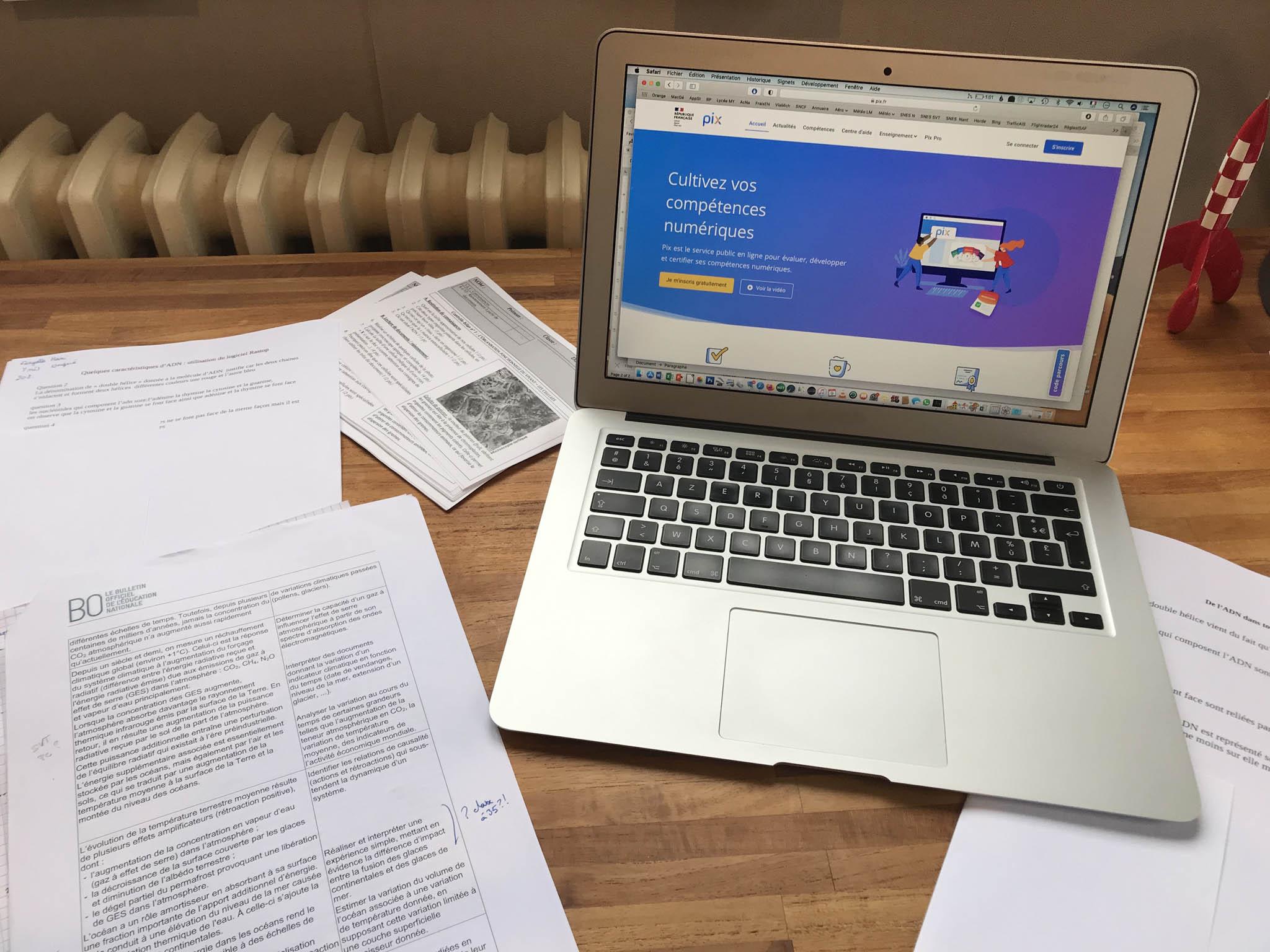 Bureau avec ordinateur ouvert sur PIX et documents variés