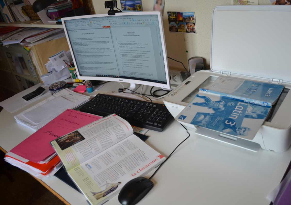 bureau d'un professeur avec un ordinateur, une imprimante et des manuels